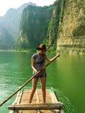 Hübsches Mädchen, das auf ein Bambusfloss schwimmt lizenzfreie stockfotos