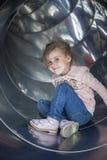 Hübsches Mädchen, das auf einem Dia im Spielplatz aufwirft stockbilder