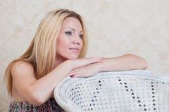 Hübsches Mädchen, das auf einem Stuhl sich lehnt und an etwas denkt Lizenzfreies Stockfoto