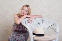 Hübsches Mädchen, das auf einem Stuhl sich lehnt und an etwas denkt Stockfotografie