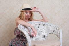 Hübsches Mädchen, das auf einem Stuhl sich lehnt und an etwas denkt Stockbilder