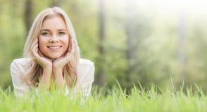 Hübsches Mädchen, das auf Gras legt Stockbild