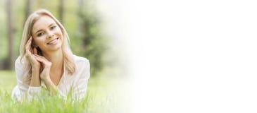 Hübsches Mädchen, das auf Gras legt Stockfoto