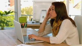 Hübsches Mädchen, das auf ihren Laptop sich konzentriert stock video