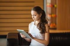 Hübsches Mädchen, das auf ledernem Sofa sitzt und Tablette hält lizenzfreie stockfotografie