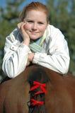 Hübsches Mädchen, das auf Pferd sich entspannt Lizenzfreie Stockfotos