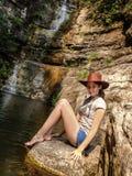 Hübsches Mädchen, das auf Stein nahe dem Wasser sitzt stockfotos