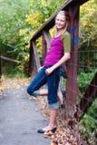 Hübsches Mädchen, das beiläufig auf Brücke aufwirft stockbild