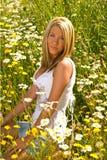 Hübsches Mädchen, das in den Feldblumen sitzt lizenzfreie stockfotografie