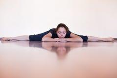 Hübsches Mädchen, das in den Spalten liegt und sich entspannt Eignungs- und Yogatrainer Stockbild