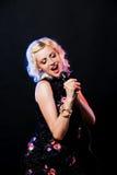 Hübsches Mädchen, das an der Partei singt auf Schwarzem Stockbild
