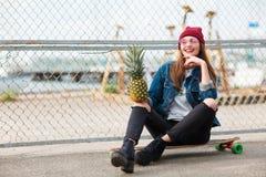 Hübsches Mädchen, das draußen mit Ananas auf dem Naturhintergrund sitzt Lizenzfreies Stockfoto