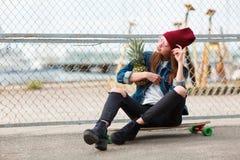 Hübsches Mädchen, das draußen mit Ananas auf dem Naturhintergrund sitzt Lizenzfreie Stockfotografie