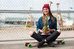 Hübsches Mädchen, das draußen mit Ananas auf dem Naturhintergrund sitzt Stockfotografie