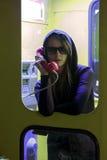 Hübsches Mädchen, das durch das Münztelefon in der Telefonzelle spricht Lizenzfreies Stockbild