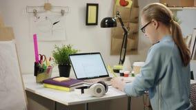 Hübsches Mädchen, das eine Hausarbeit durch Tabelle tut stock video footage