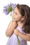 Hübsches Mädchen, das eine schöne Blume anhält lizenzfreie stockfotografie