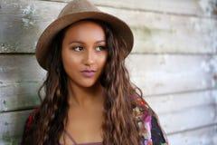 Hübsches Mädchen, das an einer hölzernen Wand sich lehnt Lizenzfreie Stockfotografie