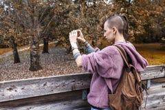 Hübsches Mädchen, das Fotos von einer Holzbrücke macht lizenzfreies stockbild