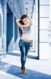 Hübsches Mädchen, das gegen einen blauen Hintergrund aufwirft stockfotografie