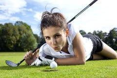 Hübsches Mädchen, das Golf auf Gras spielt Stockbild