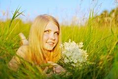 Hübsches Mädchen, das im Park mit Blumen liegt Stockfotos