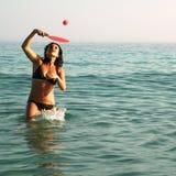 Hübsches Mädchen, das Kugel im Ozean spielt lizenzfreie stockfotos
