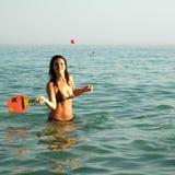 Hübsches Mädchen, das Kugel im Ozean spielt stockfotos