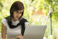 Hübsches Mädchen, das Laptop in einem Park verwendet stockbilder