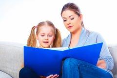 Hübsches Mädchen, das mit Buch liegt und über Weiß liest Stockfotografie