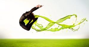 Hübsches Mädchen, das mit grünem abstraktem flüssigem Kleid springt Lizenzfreies Stockfoto