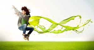 Hübsches Mädchen, das mit grünem abstraktem flüssigem Kleid springt Stockfotos