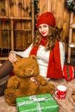 Hübsches Mädchen, das mit Weihnachtsgeschenken sitzt Lizenzfreies Stockfoto