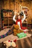 Hübsches Mädchen, das mit Weihnachtsgeschenken sitzt Stockbild