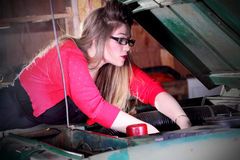 Hübsches Mädchen, das an Motor arbeitet Stockbilder
