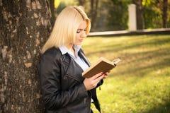 Hübsches Mädchen, das nahes Baum- und Lesebuch steht Stockfoto