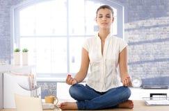 Hübsches Mädchen, das oben auf Schreibtisch meditiert Lizenzfreies Stockbild