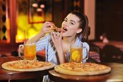 hübsches Mädchen, das Pizza isst und Bier oder ein Bierzitrusfruchtcocktail auf dem Hintergrund einer Bar oder der Pizzeria trink stockfotografie