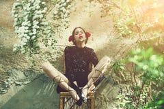 Hübsches Mädchen, das Schnürsenkel auf geflochtenem Stuhl am sonnigen Tag bindet stockfoto
