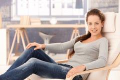 Hübsches Mädchen, das sich zu Hause beim Lehnsessellächeln entspannt Stockfoto