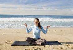 Hübsches Mädchen, das am Strand meditiert Stockfotos