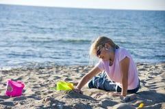 Hübsches Mädchen, das am Strand spielt Stockbilder