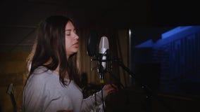 Hübsches Mädchen, das in Studio-Mikrofon singt Das Mädchen trägt Kopfhörer auf einem weißen Hintergrund Im Restlicht von Stockfotos