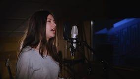Hübsches Mädchen, das in Studio-Mikrofon singt Das Mädchen trägt Kopfhörer auf einem weißen Hintergrund Im Restlicht von Stockfotografie