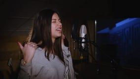 Hübsches Mädchen, das in Studio-Mikrofon singt Das Mädchen trägt Kopfhörer auf einem weißen Hintergrund Im Restlicht von Stockbilder