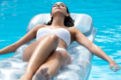 Hübsches Mädchen, das am Swimmingpool in der Sommerzeit sich entspannt Lizenzfreie Stockbilder