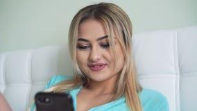Hübsches Mädchen, das am Telefon in 4K sich entspannt und spricht stock footage