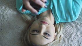 Hübsches Mädchen, das am Telefon in 4K sich entspannt und verwendet stock video