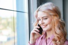 Hübsches Mädchen, das am Telefon nahe einem Fenster spricht Die goldene Taste oder Erreichen für den Himmel zum Eigenheimbesitze Lizenzfreies Stockbild