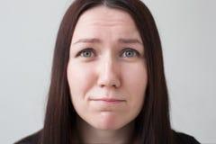 Hübsches Mädchen, das um etwas, die Stirn runzelnd ihr Gesicht bittet Stockfotografie